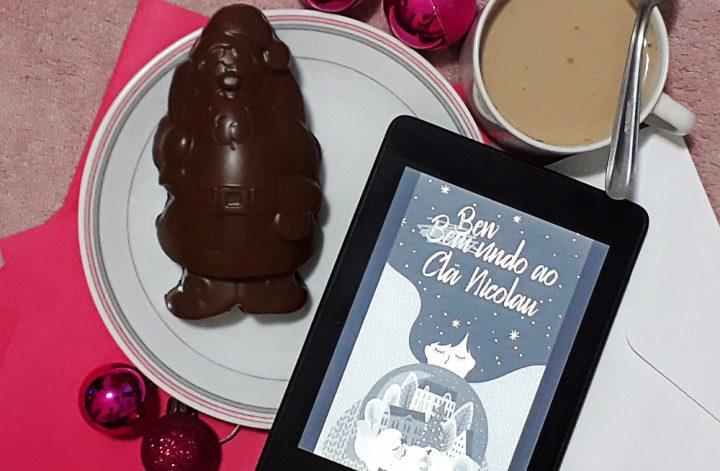 Bem-Vindo ao Clã Nicolau: foto do aparelho Kindle com a tela ligada onde a capa do livro aparece em destaque. Ao fundo, envelopes de papel brancos e cor-de-rosa, e ao redor bolas de natal rosa em tamanhos variados, uma xícara de chocolate quente e um prato contando um papai noel de chocolate.