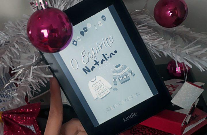 O Espírito Natalino: foto do aparelho Kindle com a tela ligada em que a capa do livro aparece em destaque. Ao fundo, galhos de uma árvora de natal branca com enfeites rosa choque variados.