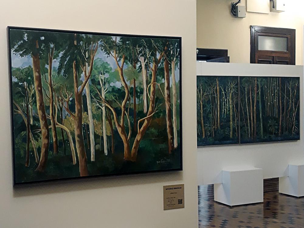 Quadro de Yara Tupynambá em primeiro plano, com painel da artista quase inteiramente visto ao fundo, ambos retratando matas com árvores finas de madeira clara e muito verde em volta.