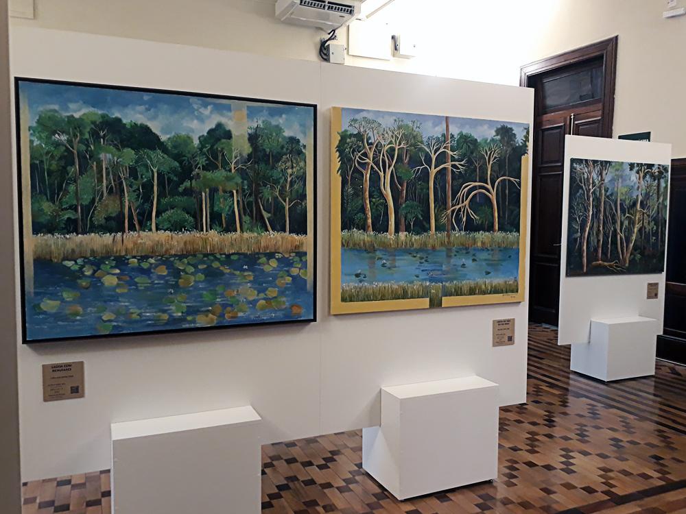 Três quadros da artista, um dois primeiro plano com lagoas em destaque na paisagem e outro ao fundo, bem semelhante à foto anterior.