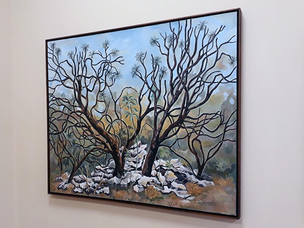 Quadro retratando árvores de galhos secos em meio a pedras claroas e algumas flores secas caídas ao redor.