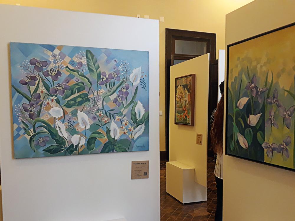 Três quadros, dois em destaque em cores claras retratando flores brancas e roxas variadas e um ao fundo, entre eles, que tem como imagem principal uma casa cercada de diversos tipos de plantas, árvores e flores, ao seu redor.