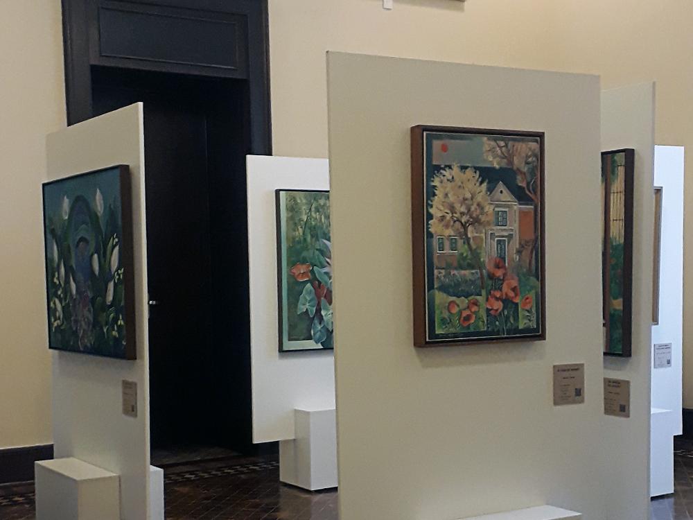 Quatro obras da sala da coleção particular de Yara Tupynambá em ângulos onde não é possível ver muitos detalhes, todas com temática principal de flores e folhas, e uma em destaque, retratando a casa (descrita na foto anterior).