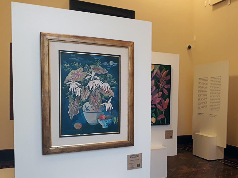 Quadro com moldura em primeiro plano, com um grande vaso onde estão folhas e flores e um menor na frente, que parece conter frutas redondas. Ao fundo, um quadro em cores complementares aparece pela metade, retratando várias folhas coloridas em fundo verde.