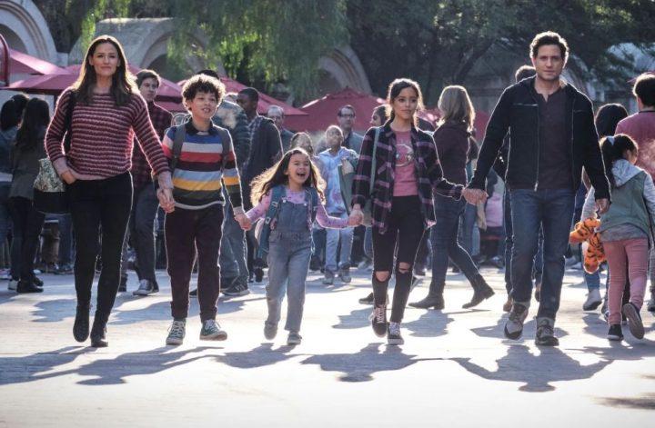 Dia do Sim: cena do filme onde a família protagonista aparece andando lado a lado em meio a uma multidão, animados, num parque de diversões.