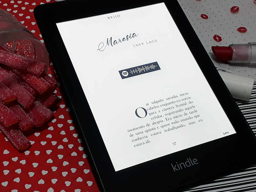 Aparelho Kindle ligado na página 57 do livro, primeira da crônica Maresia, de Luly Lage. Abaixo do título e do nome da autora há um código para ouvir a música tema no aplicativo Spotify e, em seguida, a história começa. O aparelho está inserido no mesmo cenário das outras fotos.