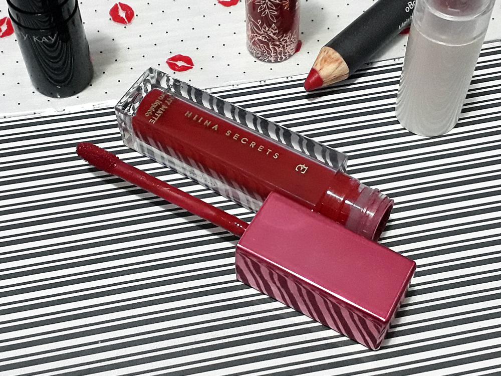Batom líquido Vermelho Hibisco da Linha Niina Secrets para Eudora, com embalada quadricular e tampa rosa. O produto está aberto, deitado, com a tampa e aplicado ao lado.