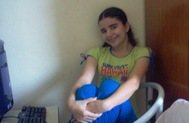 Retrato de Luly Lage, uma menina de pele clara e cabelos escuros partidos ao meio, aos 15 anos, em janeiro de 2006. Ela está sentada em uma cadeira branca, abraçada nas pernas com os pés sobre o assento, sorrindo, vestindo uma camiseta e calça de cores vibrantes. Em sua frente, aparecendo apenas parcialmente na foto, está um computador preto.