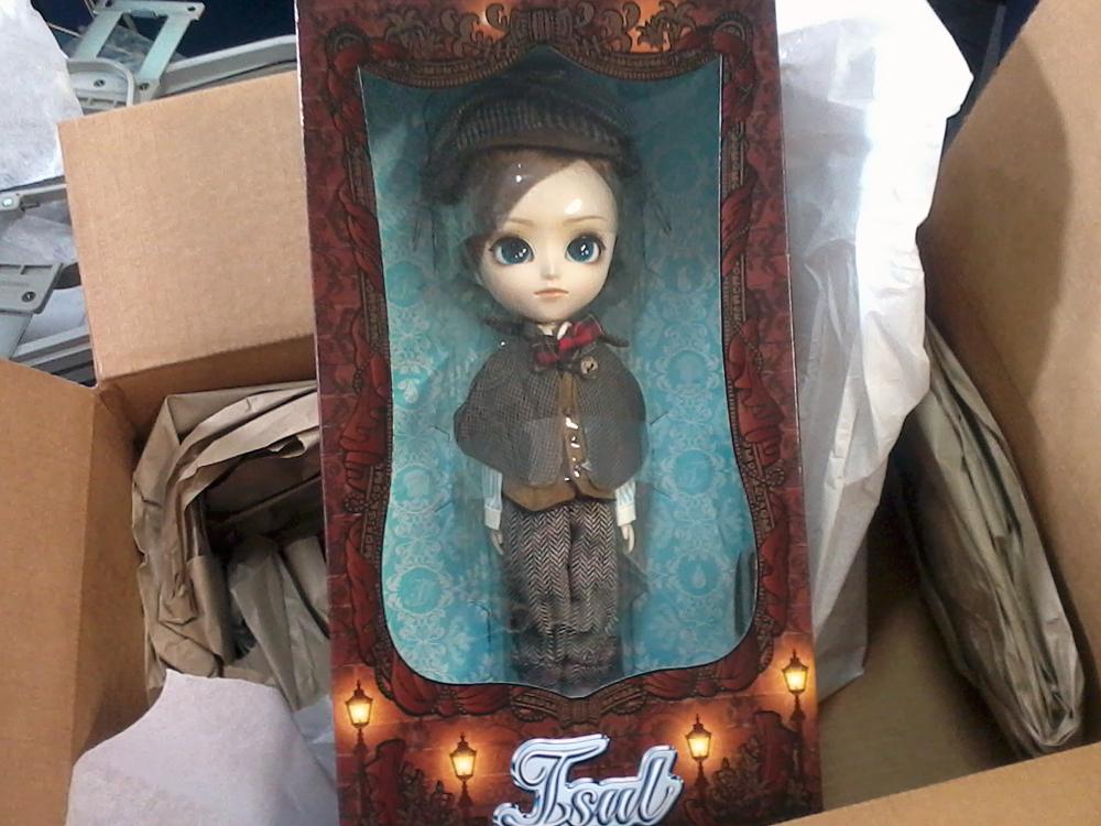 Isul Light dentro da sua caixa, de cor marrom escura com o nome do boneco em baixo junto com decorações de luminárias de rua antigas e fundo azul claro.