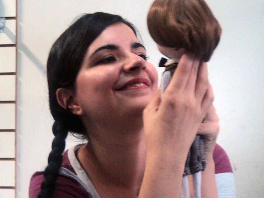 Luly Lage, uma mulher jovem de pele clara com cabelos escuros presos em duas tranças, segurando em frente ao rosto e admirando o boneco, com a expressão sorridente.